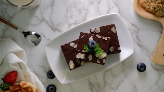 Vista dall'alto di brownies al cioccolato sul piatto bianco con e mirtilli decorati sul tavolo di marmo
