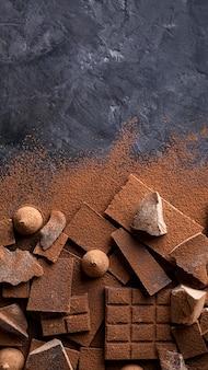 Vista dall'alto di cioccolato e caramelle con cacao in polvere e copia spazio