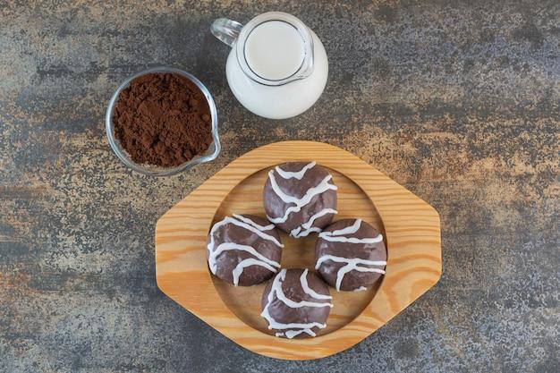 Vista dall'alto di biscotti al cioccolato sul piatto di legno con latte