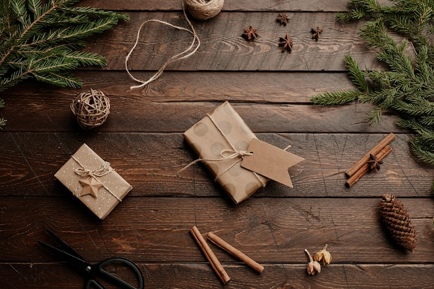 Vista dall'alto sfondo natalizio con tavolo in legno e regali rustici avvolti in uno spazio di copia di carta artigianale