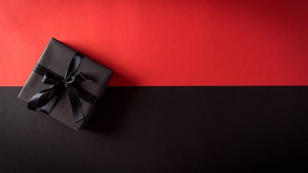 Vista dall'alto di scatole di natale con nastro nero sulla parete nera e rossa con copia spazio per il testo. composizione del black friday.
