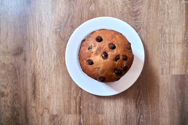 Vista dall'alto del panettone della torta al cioccolato di natale su fondo di legno con lo spazio della copia sul fuoco selettivo.