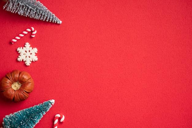 Vista dall'alto della composizione dell'ornamento della decorazione di festa di concetto di design di natale con l'albero di natale, stella del regalo con lo spazio della copia isolato sulla tavola rossa.