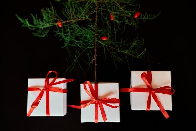Vista dall'alto natale imballaggio ecologico carta kraft e rami di abete regali per le festività natalizie su sfondo nero, luce intensa