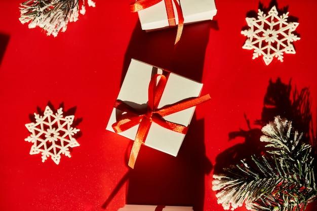 Vista dall'alto natale imballaggio ecologico carta kraft e rami di abete regali per le festività natalizie su sfondo rosso, luce intensa