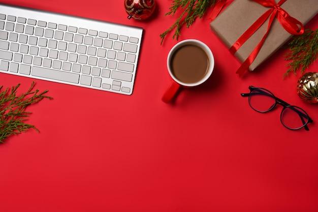 Vista dall'alto scatole regalo di natale e tazza di caffè su sfondo rosso.