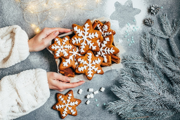 Vista dall'alto dei biscotti di panpepato di natale in una scatola in mani femminili