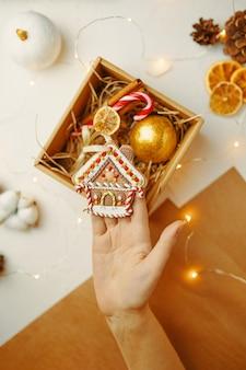 Vista dall'alto della casa di pan di zenzero di natale in confezione regalo con decorazioni festive carta da imballaggio artigianale...