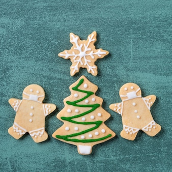 Vista dall'alto dell'albero di natale e del fiocco di neve cooikes con l'uomo di pan di zenzero che indossa la maschera sul fondo della tavola verde.