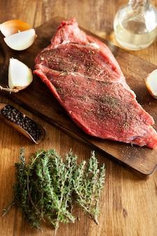 Vista dall'alto di un pezzo di carne rossa su un tagliere vintage accanto a una bottiglia di olio d'oliva vergine. carne succosa.