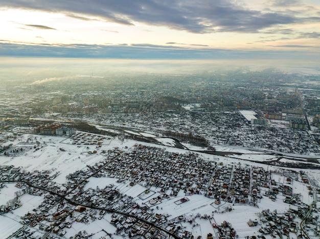 Vista dall'alto della periferia della città o delle belle case della piccola città sulla mattina d'inverno sul fondo del cielo nuvoloso. concetto di fotografia aerea con drone.