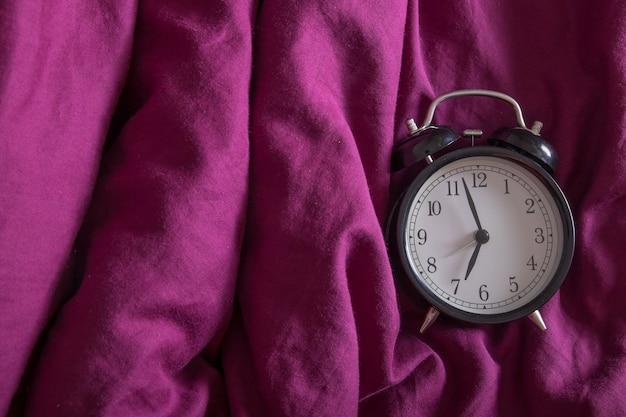 Sveglia classica vista dall'alto con l'ora del mattino su un letto colorato