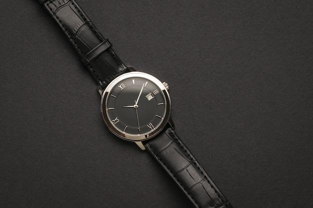 Vista dall'alto di un classico orologio da polso da uomo su sfondo nero. un accessorio da uomo alla moda e alla moda.