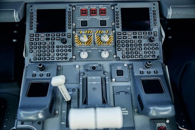 Vista dall'alto primo piano delle apparecchiature di controllo con schermi digitali e leve per l'aereo volante