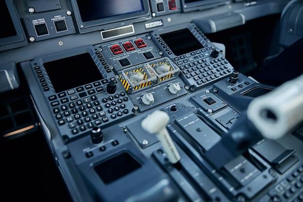 Vista dall'alto primo piano del controllo all'interno della cabina di pilotaggio con schermi e interruttori per la guida del jet