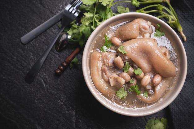 Vista dall'alto, primo piano, copia spazio, cibo di strada distintivo asiatico di taiwan, zuppa di stinco di maiale di arachidi in una ciotola di color bianco crema avorio beige isolata sul tavolo di ardesia scisto scuro