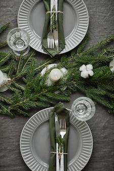 Vista dall'alto primo piano del tavolo della sala da pranzo decorato per natale con rami di abete e candele co...
