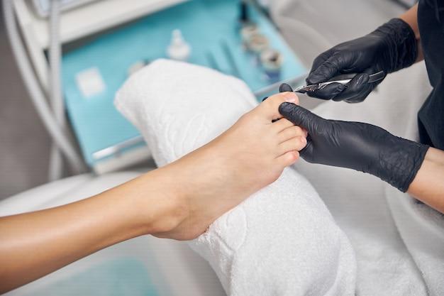 Vista dall'alto ravvicinata del piede femminile mentre l'artista delle unghie usa la pinza per cuticole per le dita dei piedi