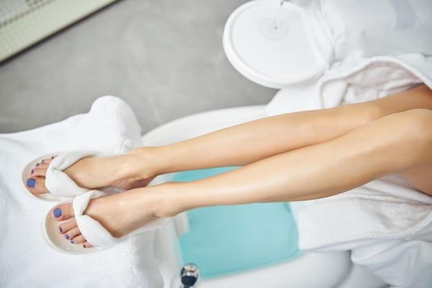 Vista dall'alto primo piano delle gambe femminili in infradito bianche che si trovano sopra il bagno in sedia per il servizio unghie