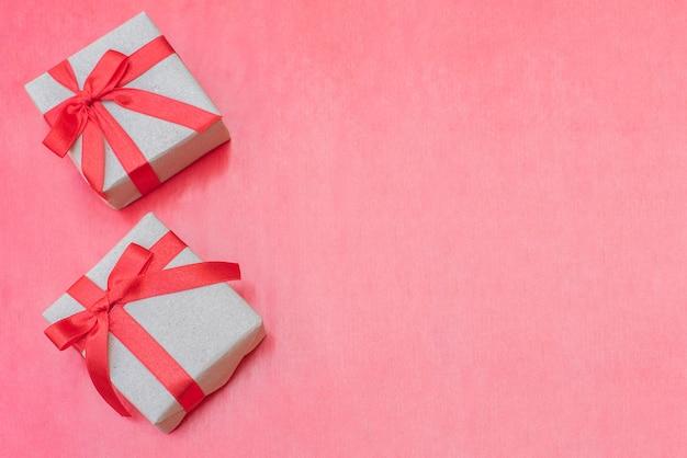 Vista dall'alto vicino confezioni regalo. arco rosso del nastro con i contenitori di regalo su fondo rosso, scatola d'annata avvolta con lo spazio della copia