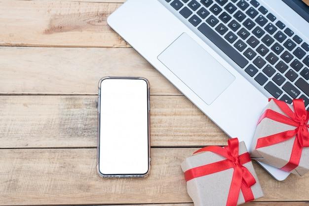 Vista dall'alto vicino scatole regalo, smartphone e laptop. arco rosso del nastro con i contenitori di regalo sulla tavola di legno, scatola d'annata avvolta con lo spazio della copia