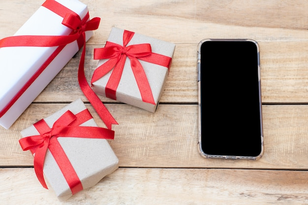 Vista dall'alto vicino confezioni regalo e smartphone. arco rosso del nastro con i contenitori di regalo sulla tavola di legno, scatola d'annata avvolta con lo spazio della copia