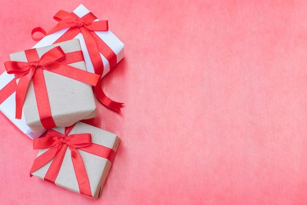 Vista dall'alto vicino tre scatole regalo. arco rosso del nastro con i contenitori di regalo su fondo rosso, scatola d'annata avvolta con lo spazio della copia