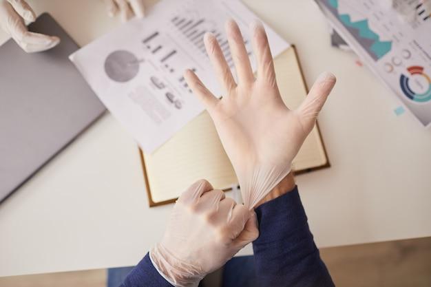 Vista dall'alto ravvicinata di un irriconoscibile imprenditore che indossa i guanti durante la riunione in ufficio, copia dello spazio