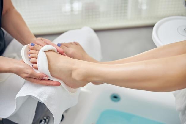 Vista dall'alto ravvicinata delle gambe della donna mentre è seduta su una sedia da pedicure con il bagno e il maestro che le mette le infradito