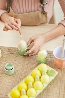 Vista dall'alto ravvicinata di una giovane donna che dipinge le uova in colori pastello per pasqua mentre è seduto a tavola in cucina, copia dello spazio