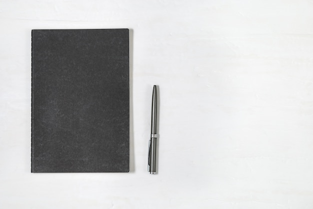 Vista superiore del taccuino chiuso nero della copertura con la penna brillante sul fondo bianco dello scrittorio. mock up quaderno. scrivania minimale con elementi decorativi.