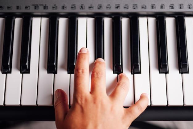 Primo piano di vista superiore di una mano femminile che gioca i tasti di un sintetizzatore elettronico
