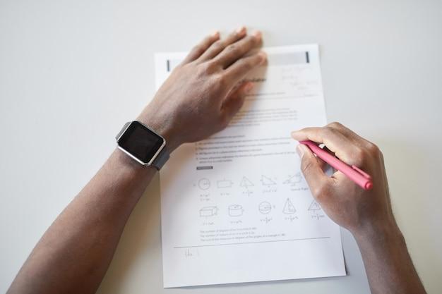 Primo piano vista dall'alto di un ragazzo afroamericano irriconoscibile che scrive sul taccuino mentre fa il test di matematica a scuola, concentrarsi su smartwatch, copiare lo spazio