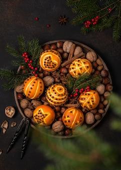 Vista dall'alto di palline di pomander arancione chiodi di garofano con motivi diversi. concetto di decorazione casalinga di natale o capodanno.