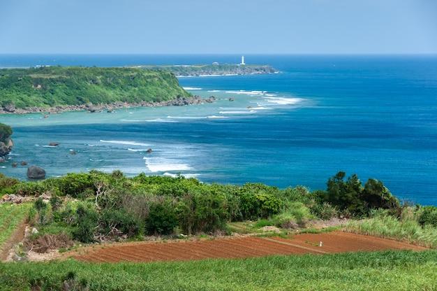 Vista dall'alto di un promontorio di costa blu profondo scogliere dell'oceano campo agricolo faro bianco lontano