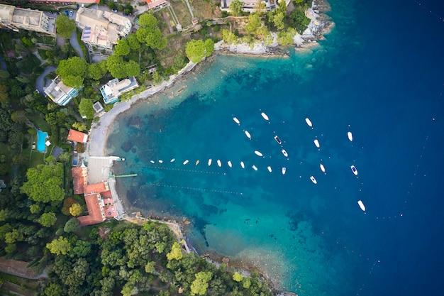 Vista dall'alto di una costa del mar ligure con acqua blu turchese con yacht bianchi e barca nel mezzo, vicino a portofino, italia
