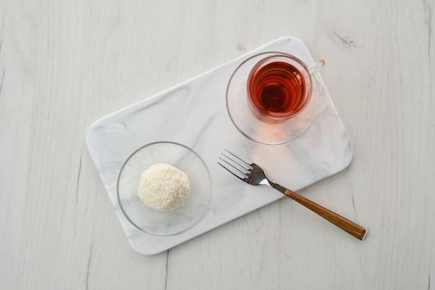 Vista dall'alto della torta di pasta biscotto al cocco e una tazza di tè su un tavolo