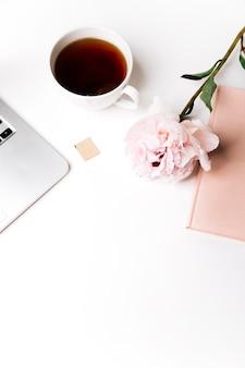 Vista dall'alto della tazza di caffè e del taccuino con fiori su sfondo bianco