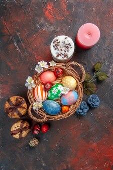 Vista dall'alto uova di pasqua colorate all'interno del cesto con biscotti su superficie scura