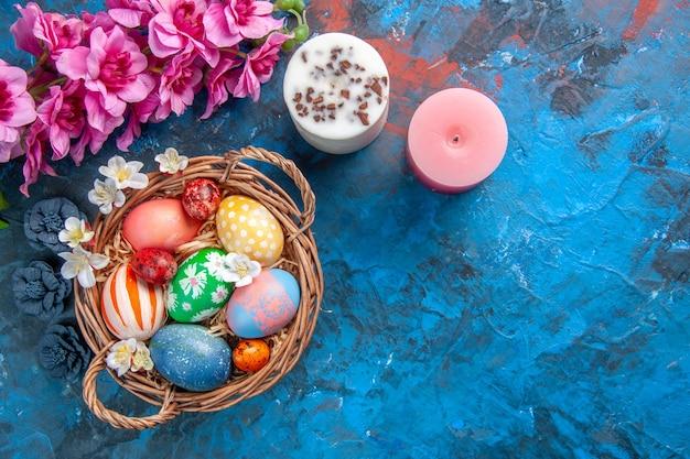 Vista dall'alto uova di pasqua colorate all'interno del cesto con fiori su superficie blu