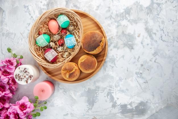 Vista dall'alto uova di pasqua colorate all'interno del cesto con fiori e candele su superficie bianca