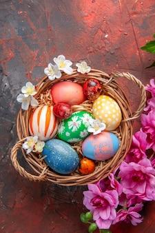 Vista dall'alto uova di pasqua colorate all'interno del cesto con fiori su superficie scura