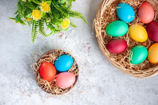 Vista dall'alto uova di pasqua colorate all'interno del piatto e cesto con fiori su superficie bianca