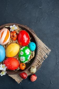 Vista dall'alto uova di pasqua colorate all'interno del piatto con paglia su superficie scura