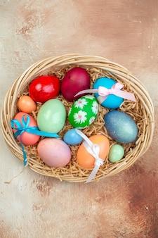 Vista dall'alto uova di pasqua colorate alcune legate con graziosi fiocchi all'interno del cesto su una superficie chiara