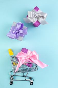 Vista dall'alto carrello mini market di piccoli regali colorati su sfondo blu