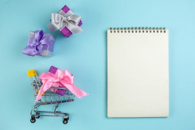 Vista dall'alto piccoli regali colorati mini taccuino del carrello del mercato su sfondo blu