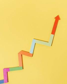 Vista dall'alto freccia colorata su sfondo giallo