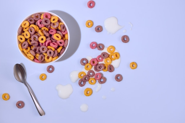 Vista dall'alto anelli di mais colorati in una ciotola su sfondo colorato viola chiaro light