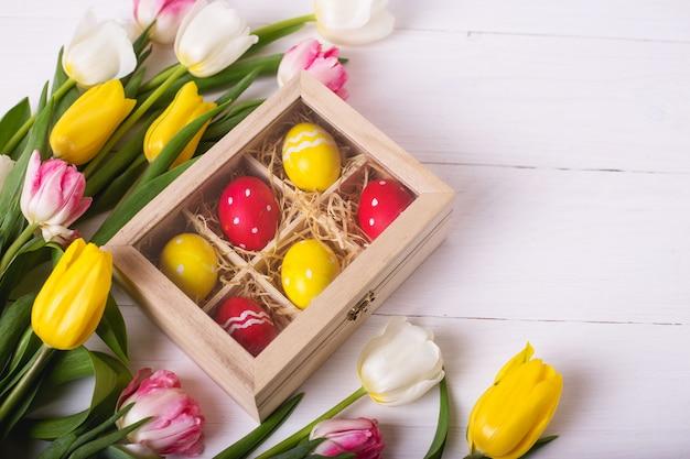 Vista superiore delle uova di pasqua variopinte su un letto di paglia in una scatola di legno lunga su una tavola di legno bianca e sui tulipani, posto per testo